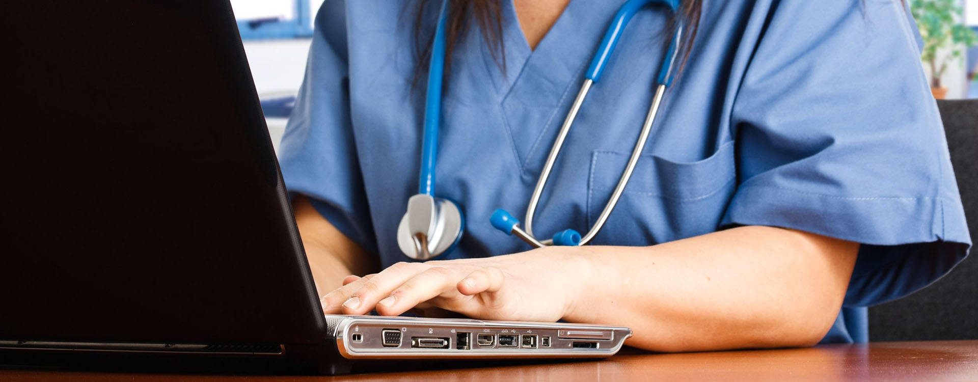 medical professional typing on a laptop