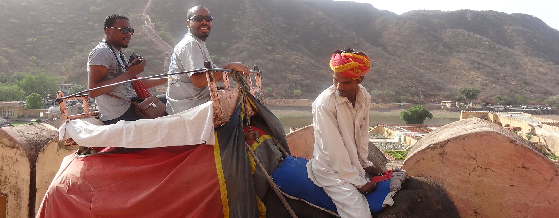 students riding a camel in India