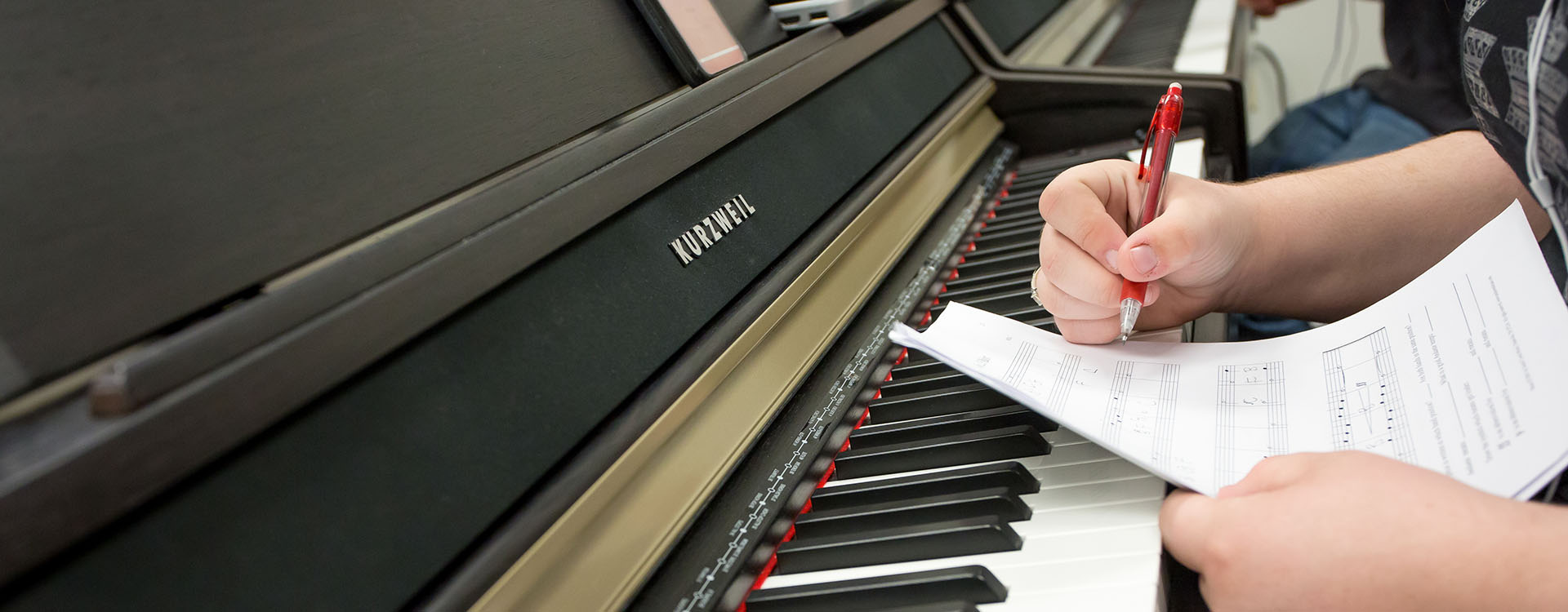 student taking notes beside a piano