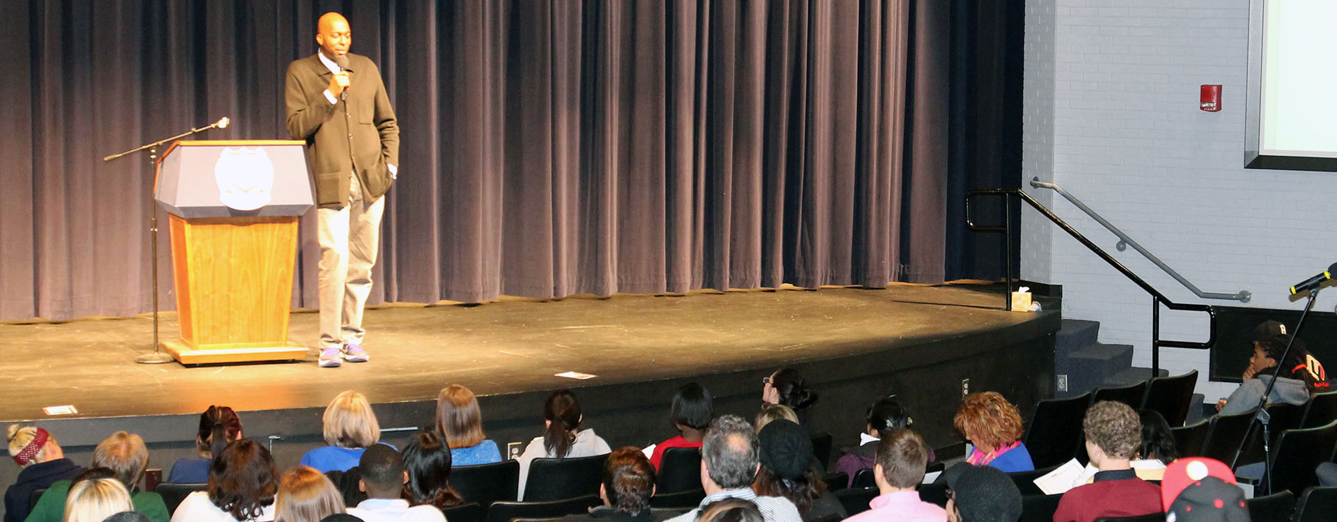 public speaker standing on stage in front of audience