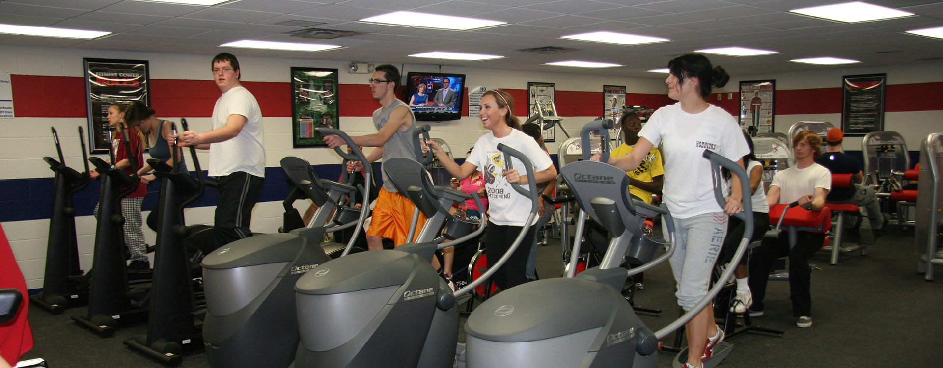 students running on treadmills in the fitness room