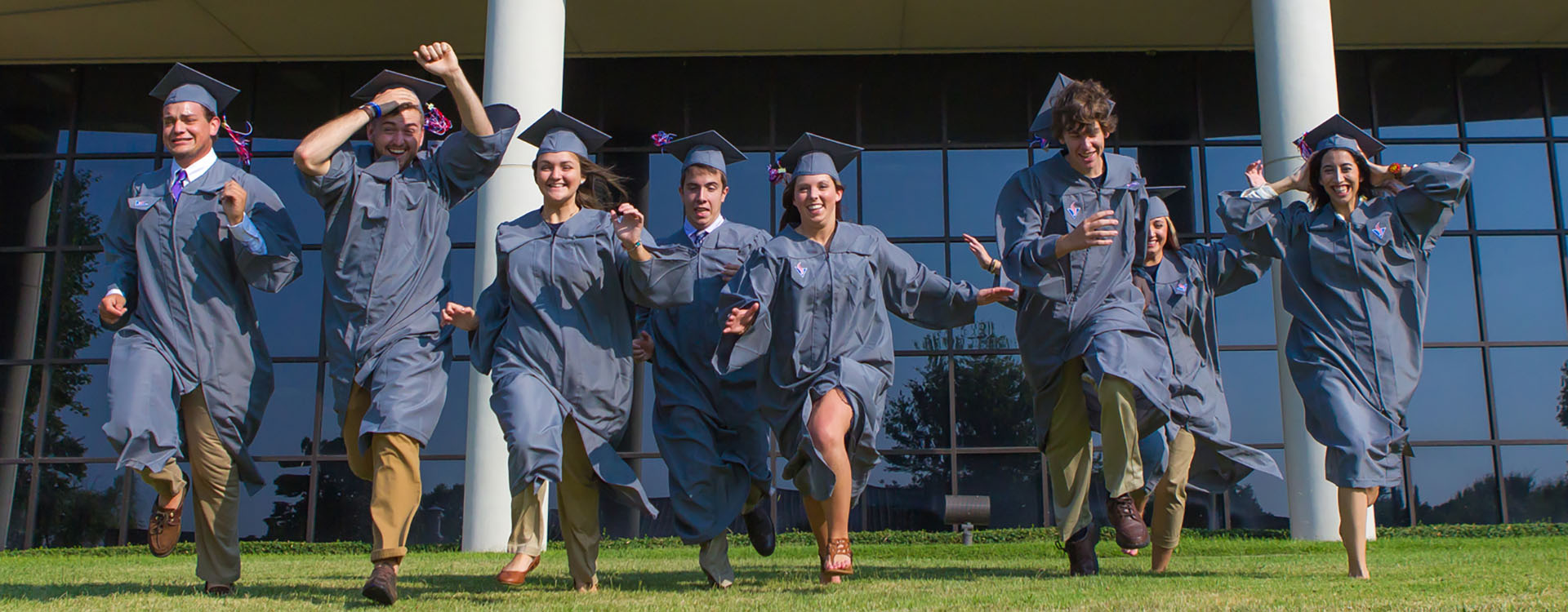 graduates running across the lawn