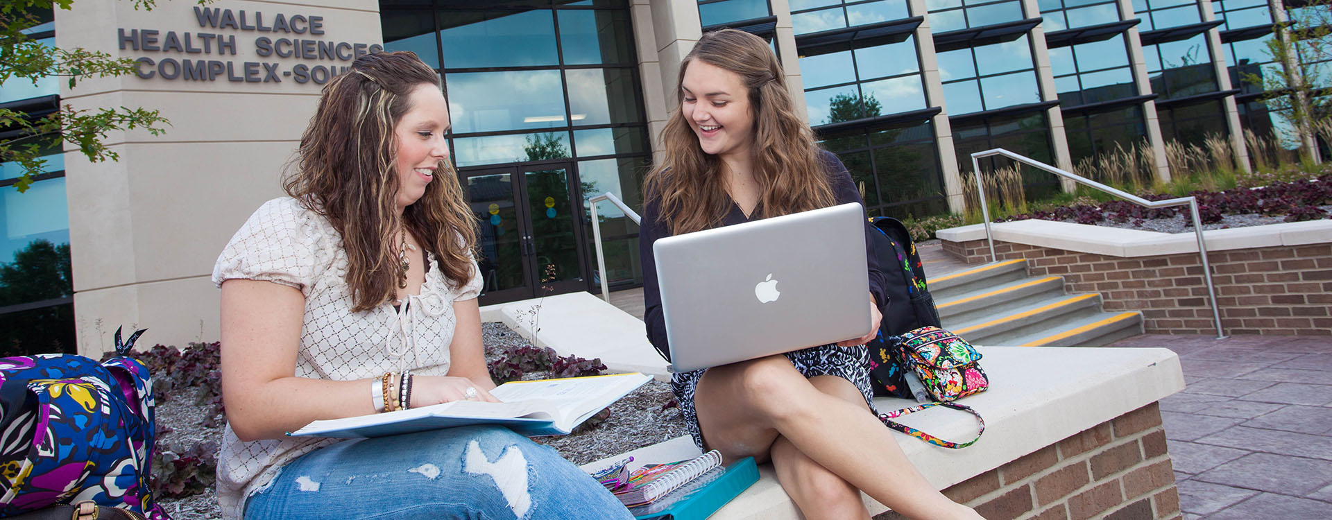 two girls sitting outside with a laptop