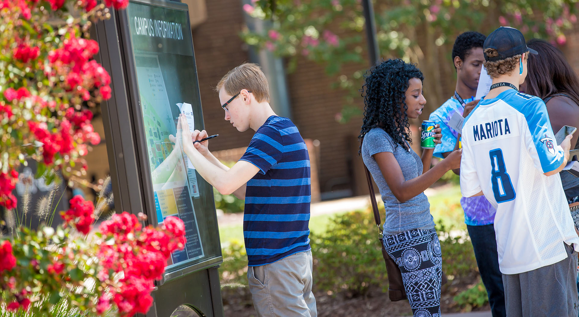 student looking at campus map sign