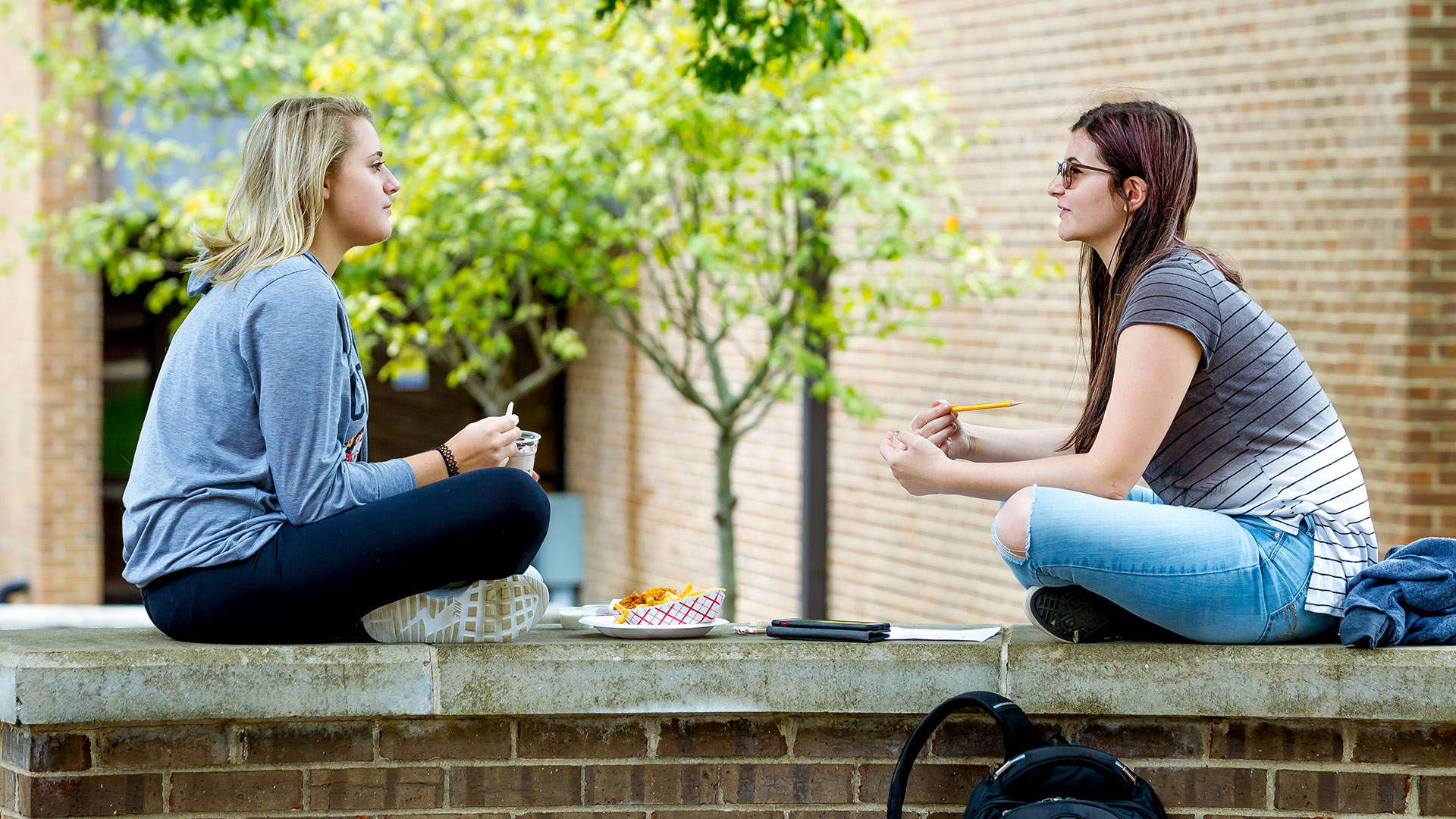 two students sitting on a wall and talking