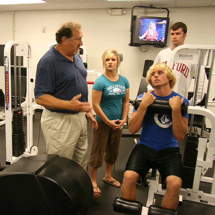 trainer working with students on fitness equipment