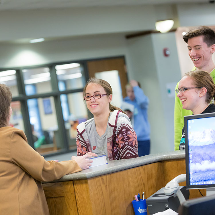 librarian assisting students at the circulation desk