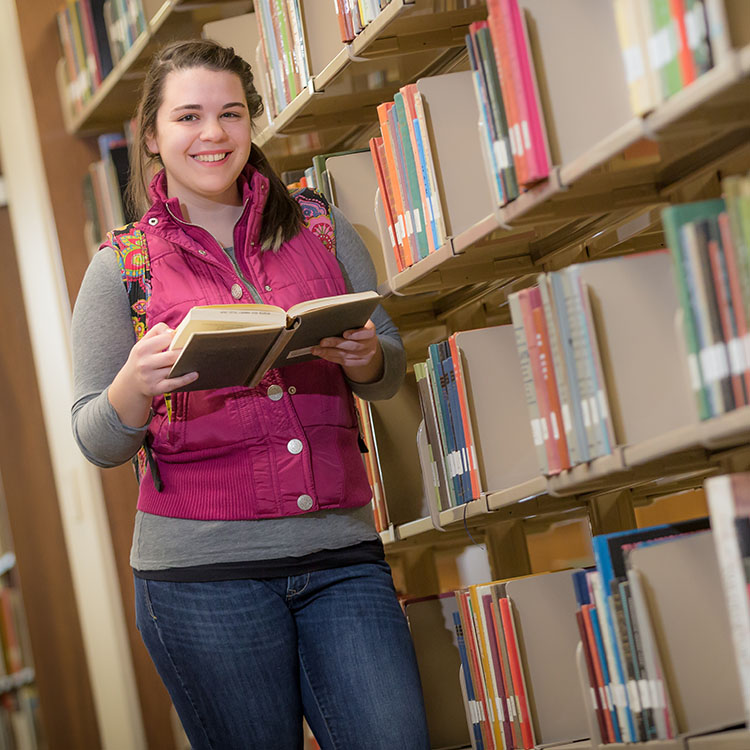 girl holding a book in the library