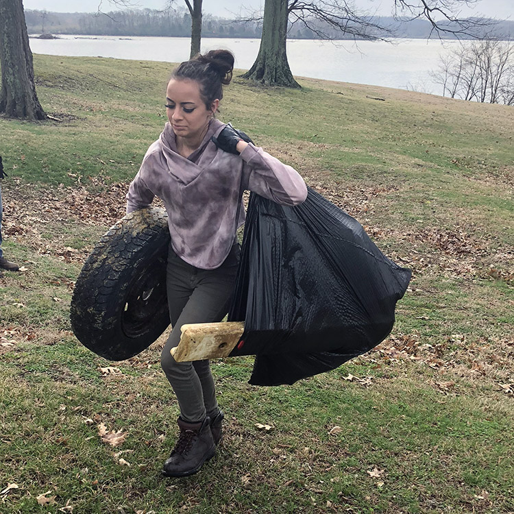 student cleaning up trash