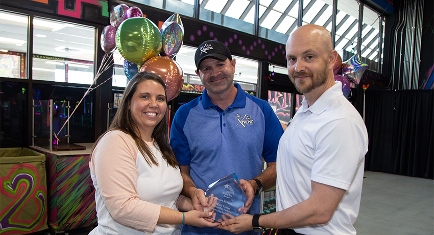 Kandace and Richard Martin, owners of All Air Xtreme Trampoline Park and Hoppity Hop Inflatables, receive the award from Charles Alexander with the TSBDC.