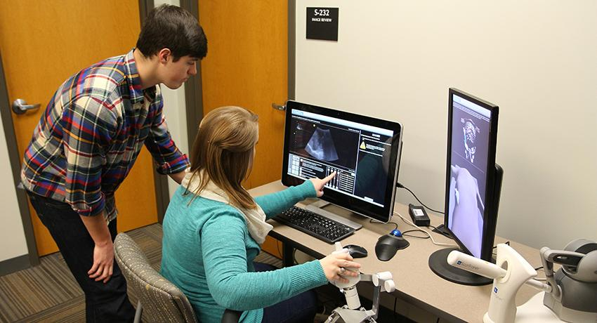 Pictured: Connor Hansford watches as Denee Kelley simulates a scan of the liver using equipment at Vol State.