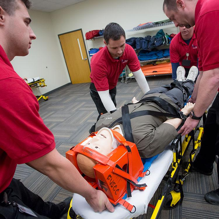 EMS students loading a dummy onto a stretcher