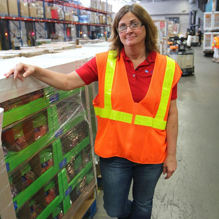 woman wearing orange vest standing in a warehouse