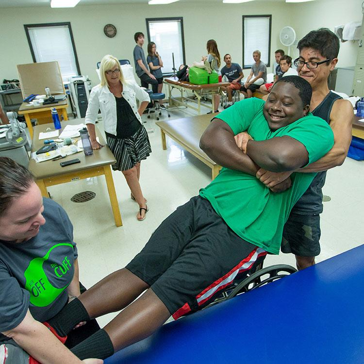 students lifting another student onto a table