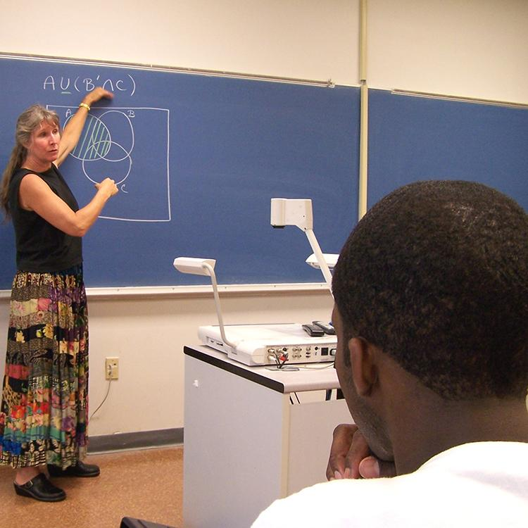 teacher explaining math problem on the board