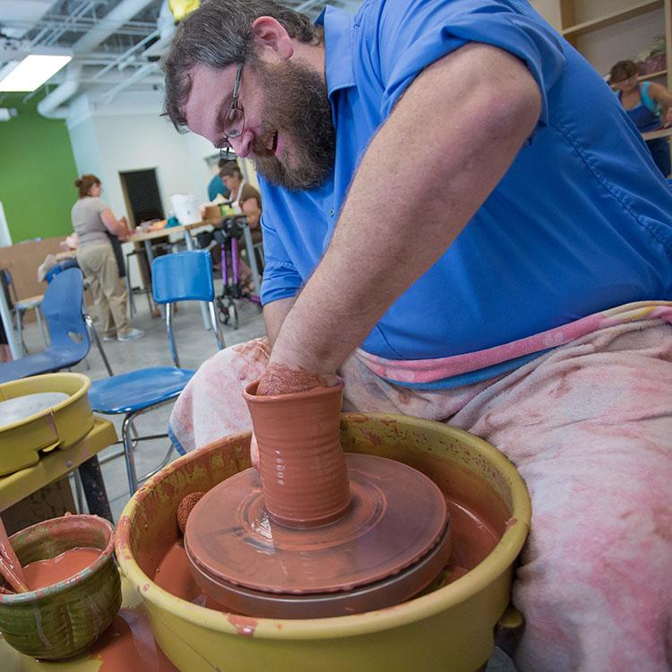 student working with clay on a pottery wheel