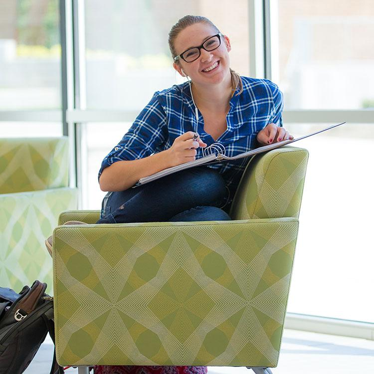 girl with glasses and a book, sitting in a chair and smiling